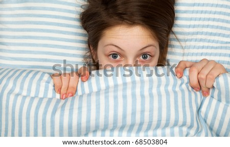Young Teenage Girl Looking Scared in Bed - stock photo