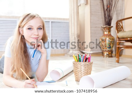 young teenage girl on the floor thinking and drawing - stock photo