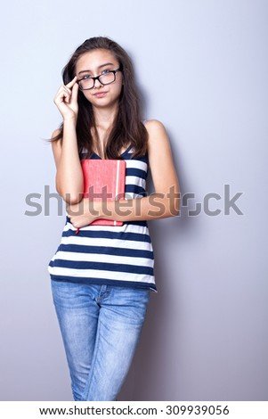 Young teenage girl posing with book, wearing fashionable eyeglasses. - stock photo