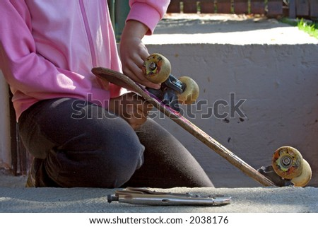 young teenage girl repairing a skateboard