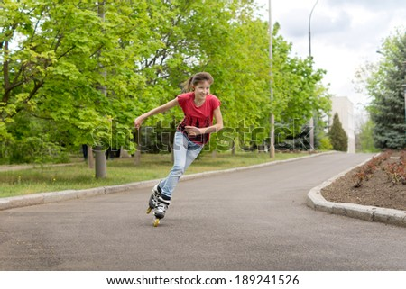 Young teenage girl roller skating around a bend in a country road at speed leaning into the turn with her arms flying as she enjoys practising her hobby - stock photo