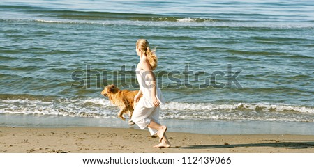 Young teenage girl running with her golden retriever along the beach shore.