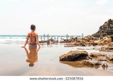 Young teenage girl sitting on the beach of Atlantic ocean. Multicolored summertime outdoors horizontal image. Tenerife, Canary Islands, Spain. - stock photo