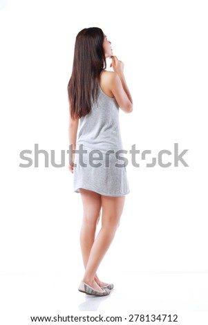 Young teenage girl standing and looking on something. Back pose