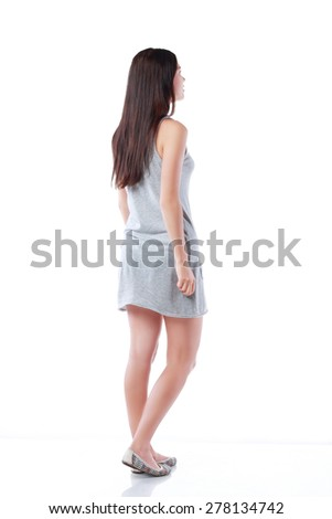 Young teenage girl standing and looking on something. Back pose, full length