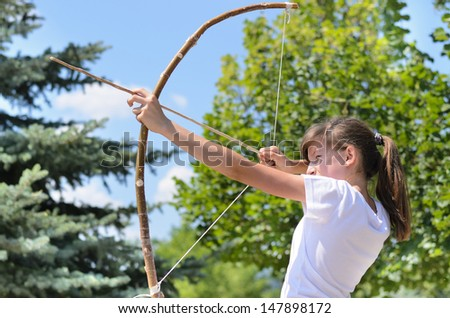 Young teenage girl standing sideways to the camera taking aim with a bow and arrow - stock photo