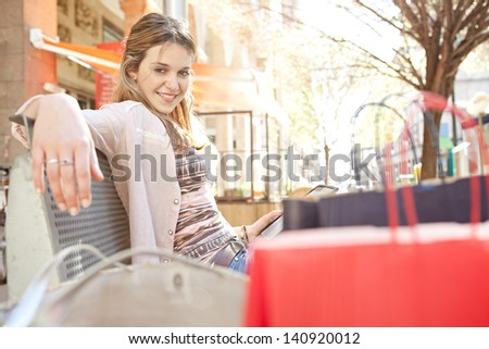 Young teenage girl student sitting on a city bench in the shopping district holding a digital tablet pad, with her paper shopping bags in the foreground, smiling. - stock photo