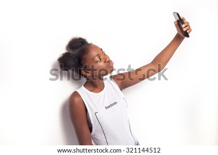 Young teenage girl taking photo by mobile phone. Studio shot. - stock photo