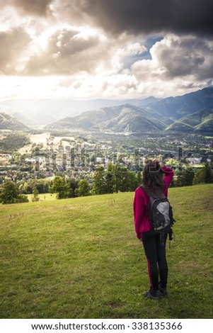 Young teenage girl tourist looking at little town in valley ang beautiful mountain landscape background - stock photo