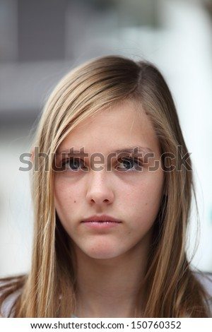 Young teenage girl with a serious expression and long blond hair looking directly at the camera - stock photo