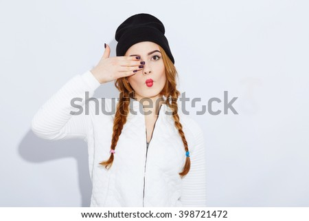 Young teenage red-haired girl with long hair wearing white shirt and black hat, stylish haircut and makeup, red lips, pathos emotion, posing. - stock photo
