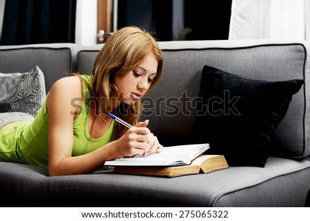 Young teenage woman learning to exam on a sofa. - stock photo