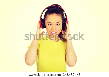 Young teenage woman with headphones listening to music.