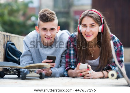 Young teenager and his happy girlfriend with they smartphones outdoors  - stock photo