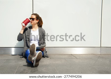 Young teenager drinking coffe and looking aside with tablet - stock photo