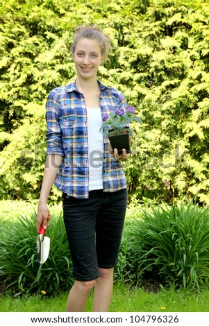 Young teenager gardening and having purple flowers in hands