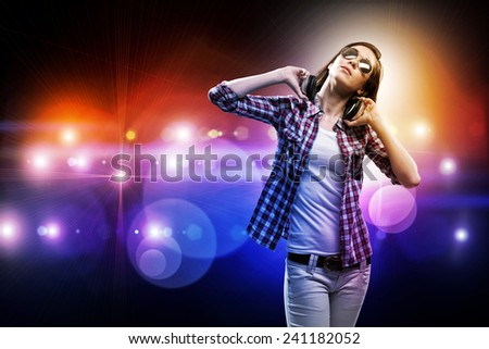 Young teenager girl in shirt wearing headphones in stage lights - stock photo