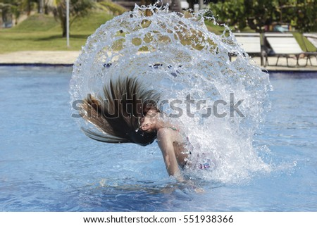 Young teenager girl playing in the swimming pool