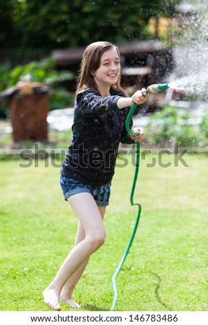 Young teenager having a water fight in the garden - stock photo