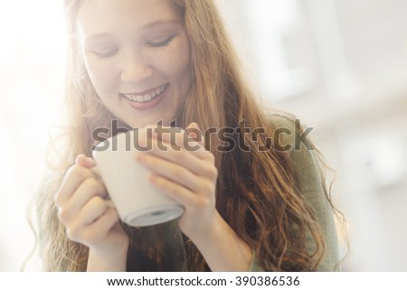 Young teenager holding a cup of coffee - stock photo