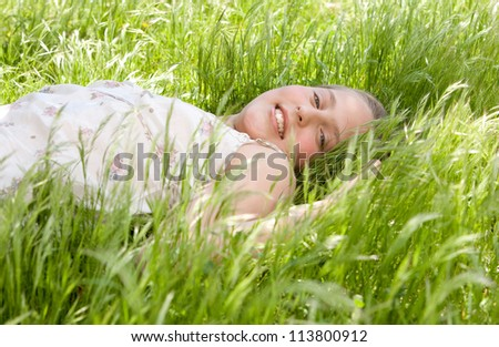 Young teenager laying down on a long green grass garden, smiling at the camera. - stock photo