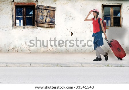 Young teenager on travel destination with luggage wolking beside two old wooden windows and rough wall of mud - stock photo
