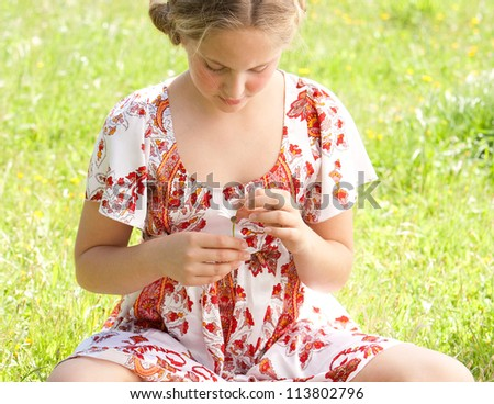 Young teenager pulling petals off a daisy flower, playing at love me love me not. - stock photo