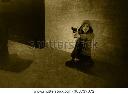 young teenager woman abused suffering internet cyberbullying scared screaming desperate in fear face expression sitting on the floor pointing gun to computer monitor in cyber bullying - stock photo