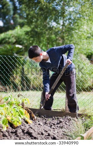 Young teenager working in the garden - stock photo