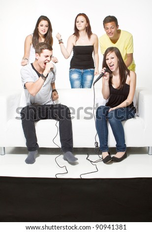 Young teenagers playing a singing video game. Enjoying themselves. Having fun! - stock photo