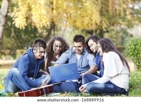 Young teenagers sitting in the park with laptop and discussing - stock photo