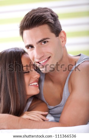 Young tender couple relaxing in bed - stock photo