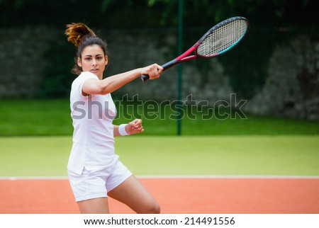 Young tennis player hitting ball on a sunny day - stock photo