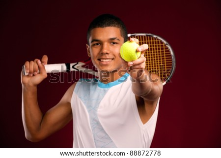 Young tennis player holding a ball and racket. studio shot - stock photo