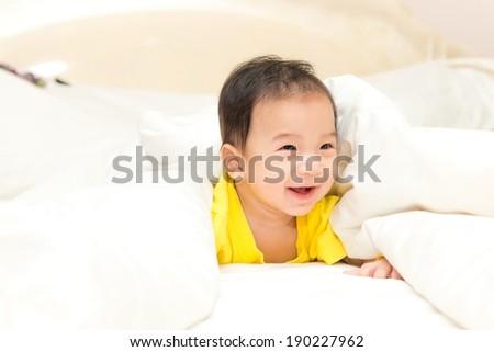 Young Thai baby boy in yellow shirt posing various actions, taken indoor - stock photo