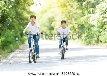 Young Thai boy ride bicycle on the road in the park.