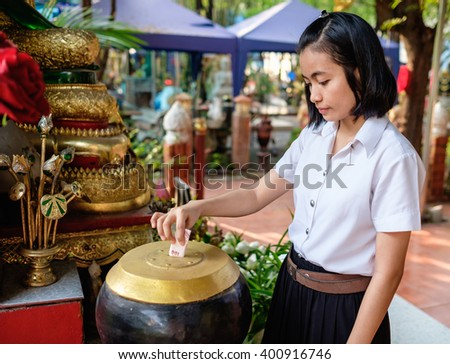 young thai girl student in uniform donate money for buddhism temple in Thailand - stock photo