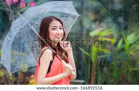 young Thai lady standing with under umbrella under rainning - stock photo