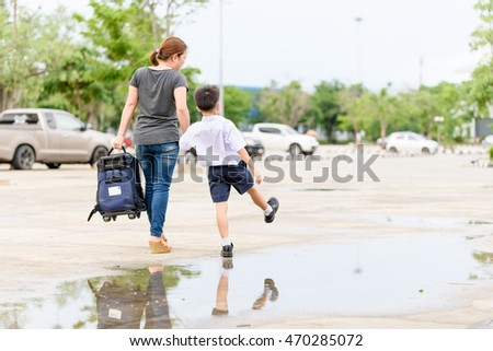Young Thai student boy in school uniform walk with his mom on the road with the reflection from the water.