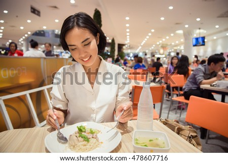 young thai woman eating rice in restaurant