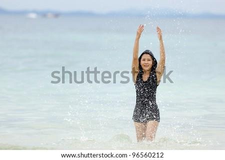 young thai woman splashing Water in andaman sea, thailand - stock photo