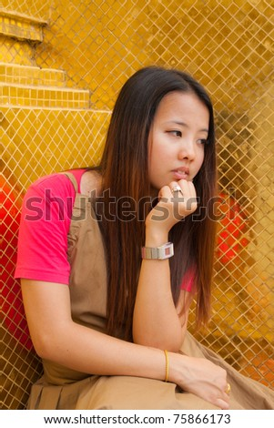 Young Thai women distracted and rest her chin on hand with golden tile texture in background - stock photo