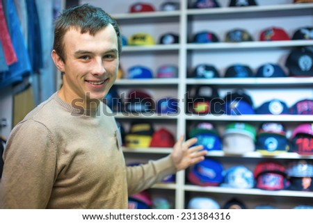 Young the man in shop at a counter with caps - stock photo