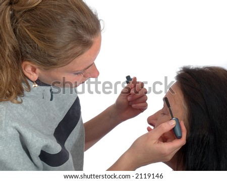 Young the stylist prepares for lady for photographing on a white background - stock photo