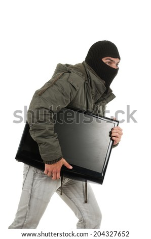 young thief wearing black hood and jacket carrying a monitor isolated on white