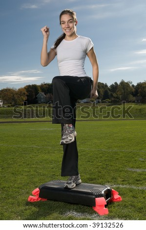 Young thin woman exercising outdoors, doing step aerobics - stock photo