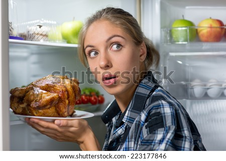 Young thin woman with fearful glance standing near opened refrigerator and holding fried chicken at night - stock photo