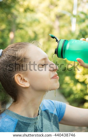 Young thirsty girl after training pour out water on face from a bottle