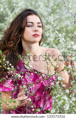Young thoughtful brunette touching branches of flowering tree - stock photo