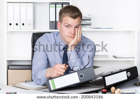 Young thoughtful businessman is sitting in front of many files on his desk in the office. A shelf is in the background. The man is looking to the camera. - stock photo